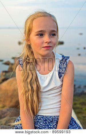 Portrait of little beautiful girl on sunset
