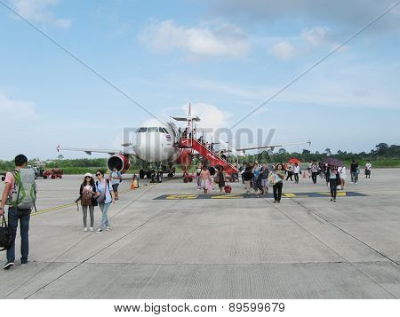 NATHON SI THAMMARAT, THAILAND - OCTOBER 18, 2013: Aircraft and passengers on airfield of airport.