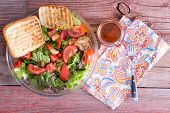 stock photo of brew  - Healthy mixed leafy green salad with lettuce tomato garlic sesame and bell peppers served with grilled toast and freshly brewed tea on a rustic wooden table and napkin overhead view - JPG