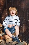 picture of denim wear  - Cute little blond boy sitting on cut wood and leaning on an old wooden wall - JPG