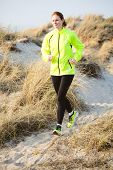 image of dune grass  - A young woman runs cross country through a beach with dunes and grass. ** Note: Visible grain at 100%, best at smaller sizes - JPG