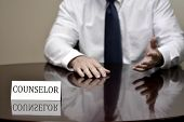 stock photo of motivation talk  - Man at desk with folded hands business card for Counselor to talk and help people - JPG
