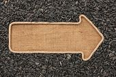 foto of sackcloth  - Pointer made from rope with sunflower seeds lying on sackcloth with space for your text - JPG