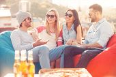 pic of foreground  - Four young cheerful people chatting while sitting at the bean bags on the roof of the building with pizza and beer laying on foreground - JPG