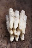 stock photo of white asparagus  - bunch of raw white asparagus on wood - JPG