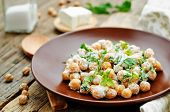 foto of chickpea  - salad with chickpeas feta and parsley on a dark background