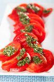 pic of pesto sauce  - Salad of sliced tomatos with pesto sauce close up - JPG