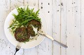 stock photo of veggie burger  - Swiss chard veggie fritters with mash potatoes and rocket leaves on white plate fork and knife and white rough background copy splace - JPG