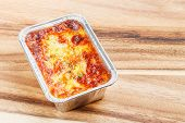 foto of lasagna  - Close up beef lasagna in foil tray on wooden chopping board deep focus image delicatessen - JPG
