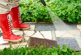 pic of pressure-wash  - Person in red gumboots cleaning garden alley with a pressure washer - JPG