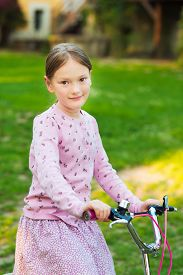 image of grils  - A sweet little gril sitting on her bycicle in the park at sunset - JPG