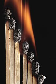 stock photo of combustion  - combustion of several matchsticks on black background - JPG