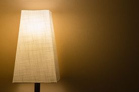 picture of lamp shade  - A lamp with a cloth lamp shade in a dark room against a simple wall - JPG