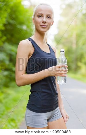 Smiling young woman having her break after running