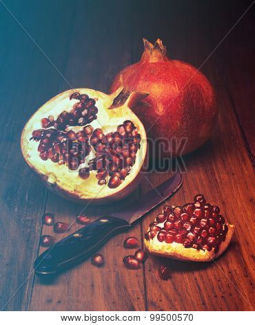 juicy pomegranate open on wood board. Filtered image: vintage effect.