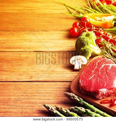 Raw steak on the wooden board.Filtered image: warm cross processed vintage effect.