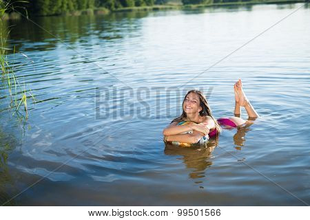 Young happy smiling girl hugging big ball splashing in lake