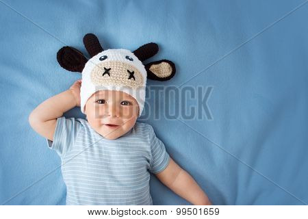 Baby in a cow hat on blue blanket