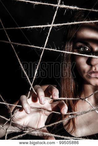 Beautiful Young Woman Behind The Interlaced Ropes