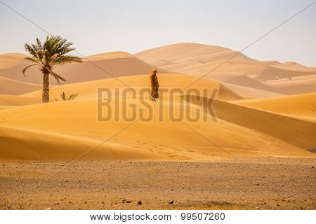 MERZOUGA, MOROCCO, APRIL 13, 2015: Local man walks on sand dunes