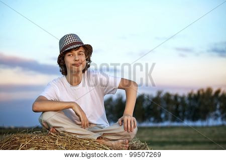 teenager on a haystack in the field in autumn