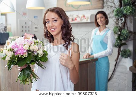 Beautiful young woman likes flowers in store
