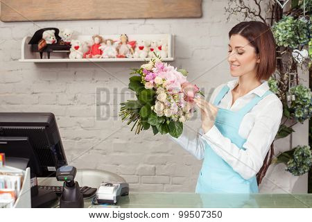 Attractive young saleswoman is working in flower shop