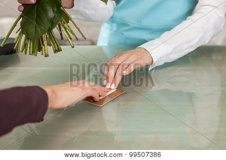 Skilled saleswoman is serving her client in flower shop