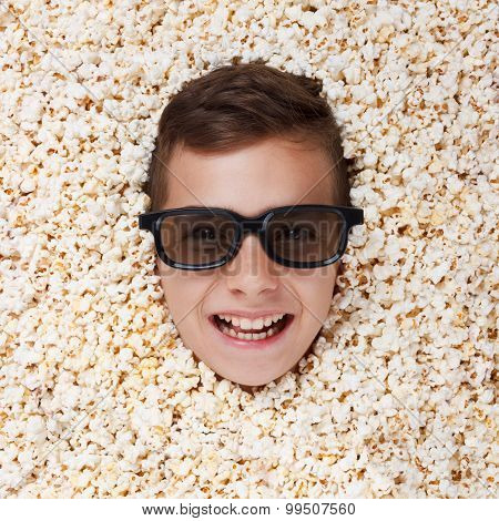 Smiling young boy in stereo glasses looking out of popcorn
