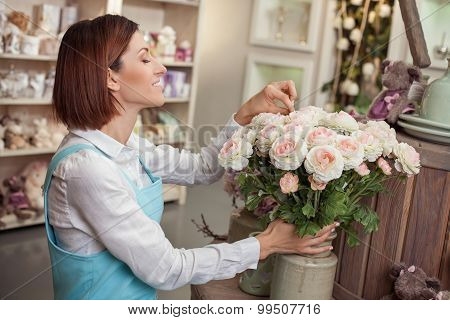 Beautiful young florist is working in her store