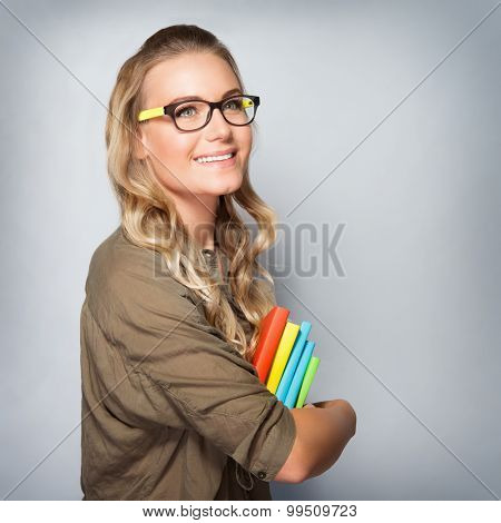Portrait of cute blond student girl over gray background, wearing glasses and holding in hands colorful books, back to school