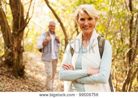 happy mid age woman hiking with husband in forest