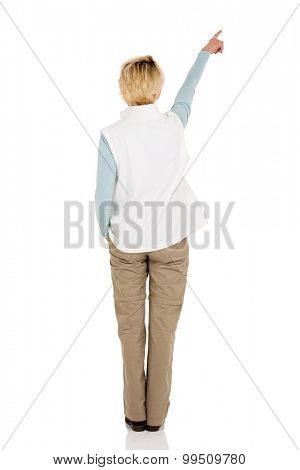 rear view of middle aged woman pointing at empty copy space