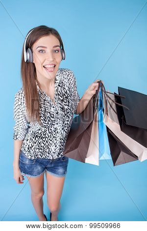 Attractive young girl with packages and earphones
