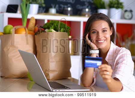 Smiling woman online shopping using tablet and credit card in kitchen