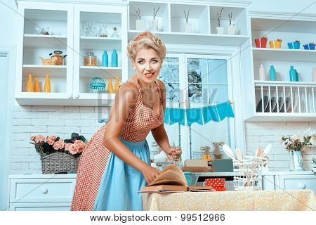 Girl In Old-fashioned Style, And Stands  Kitchen Preparing Meal.