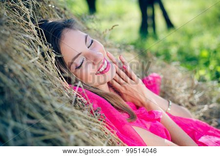 Excited young lady in pink dress relaxing on hay