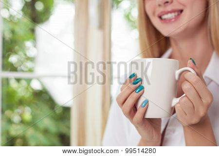 Attractive young woman is enjoying hot drink
