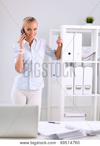 Young business woman standing in office talking on her mobile phone