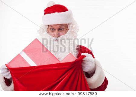 Cheerful Santa Claus is carrying a bag of presents