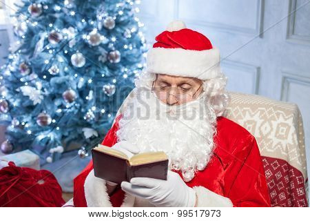 Cheerful Santa Claus is resting near a holiday tree