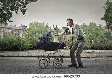 Businessman shouting into his son's cradle through a megaphone
