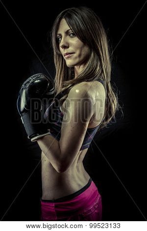 Muscular, strong woman athlete with boxing gloves