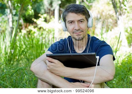young man holding a tablet with headphones, outdoor