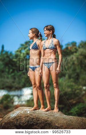 two young girls on stones on a beach