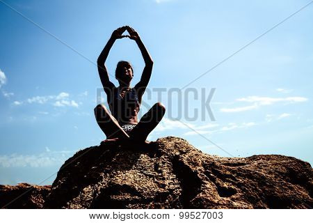 girl practising yoga on beach