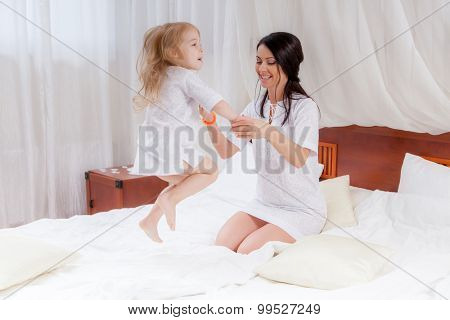 mother and little daughter jumping on bed