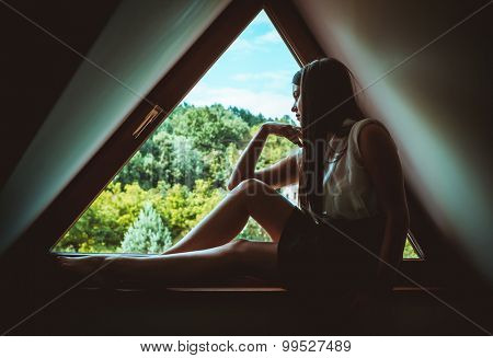 Young lonely woman sitting on a window