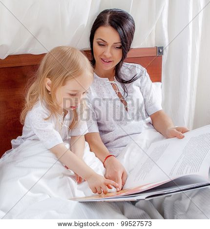 Mother and her daughter looking at a book on the bed