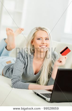 Young and happy woman with a credit card. Online shopping concept.